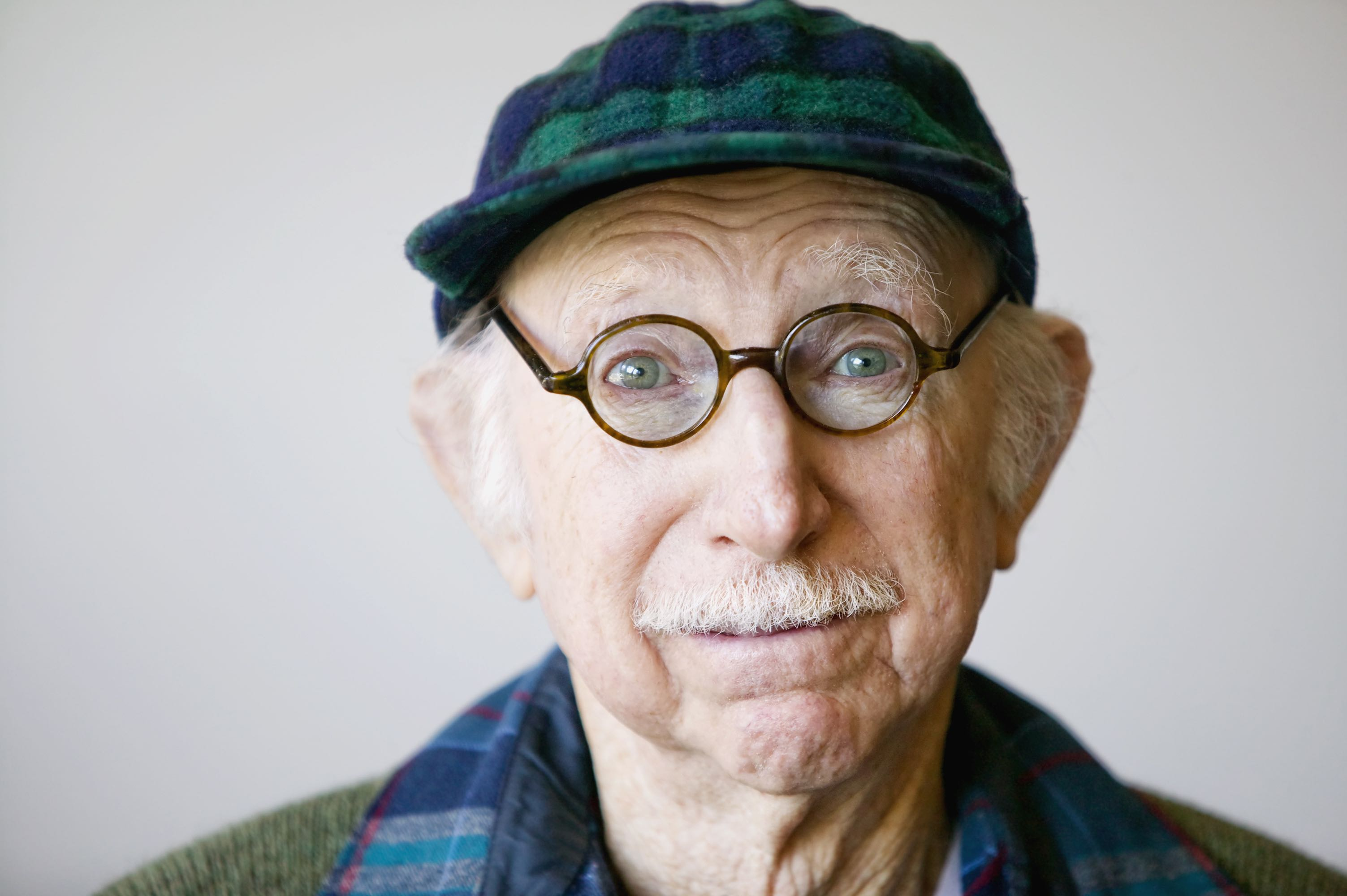 Portrait of a senior citizen wearing glasses and a sweater.
